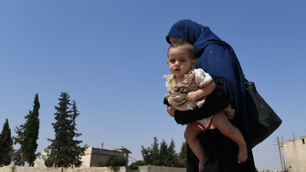 A Syrian woman holds her child walks at the Abu Duhur crossing on the eastern edge of Idlib province