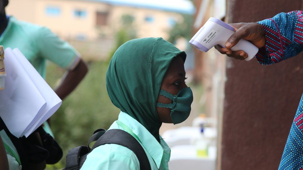 Schoolgirl having her temperature taken