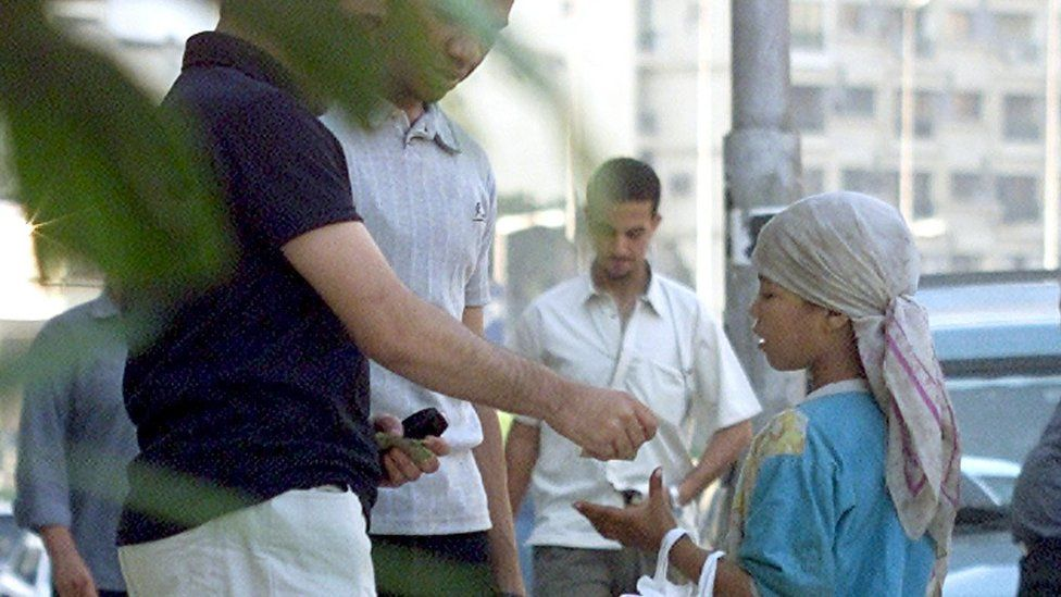 Men give money to a young beggar in Cairo (file photo)