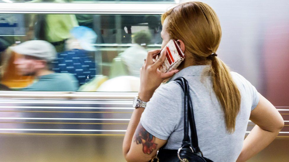 Woman on the phone on the New York subway