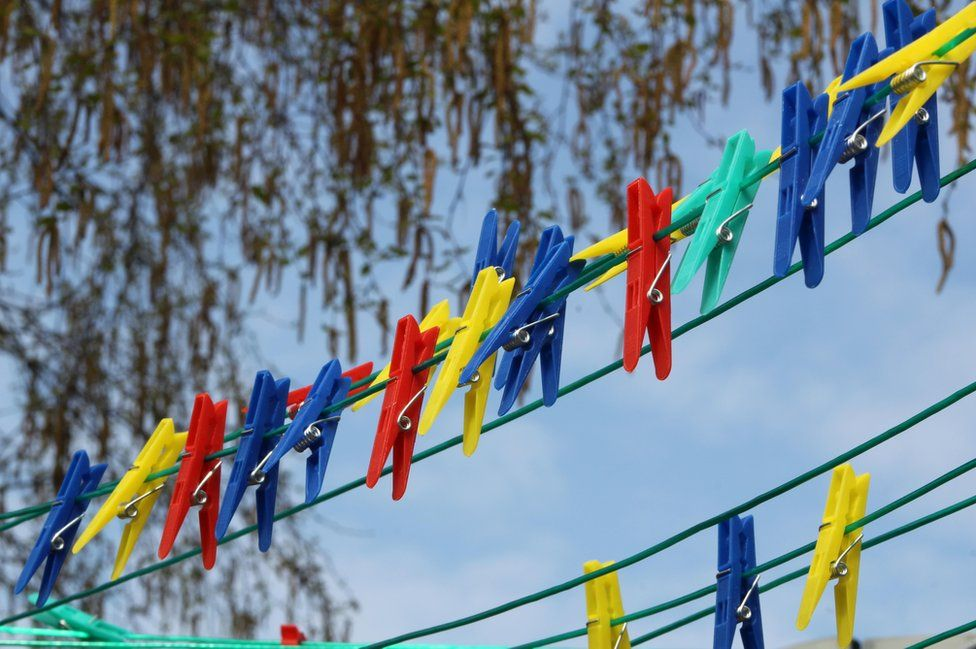 Colourful pegs on a line under a tree