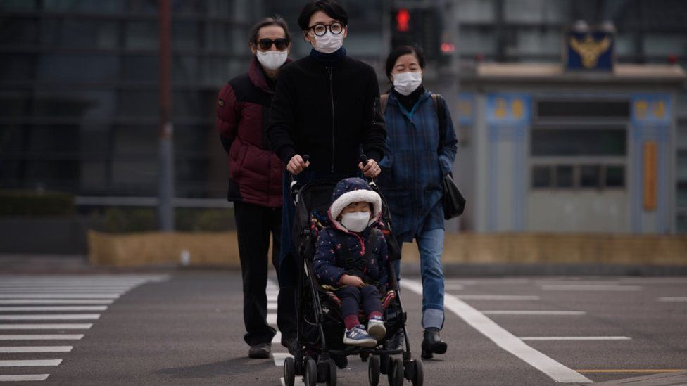 Korean family with little child, all wearing face masks