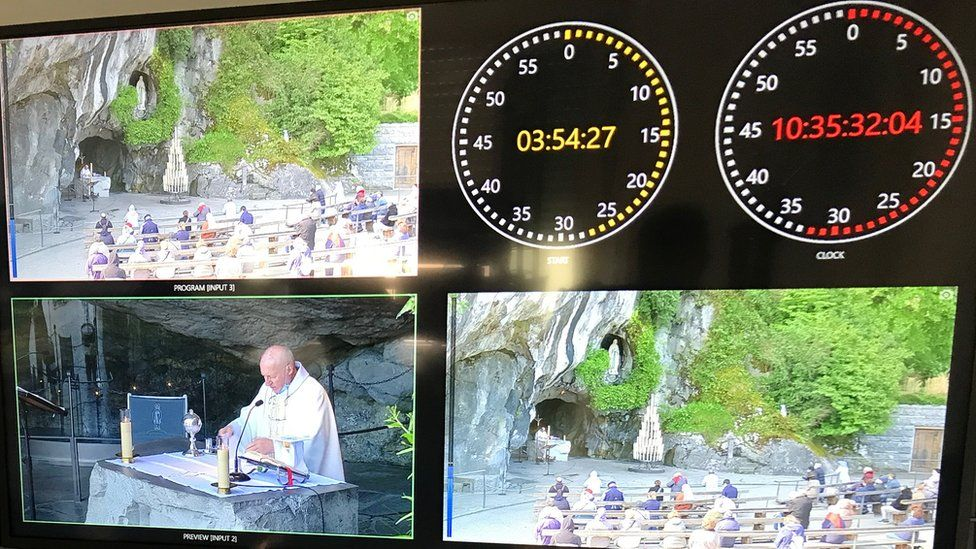 Screens showing the broadcast of a religious service