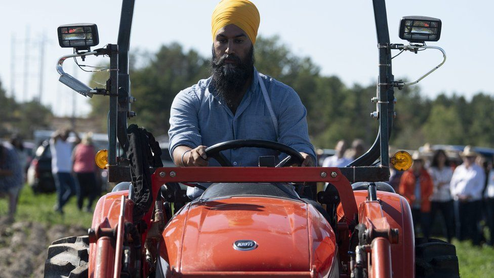 NDP leader Jagmeet Singh drives a tractor as he campaigns in Ontario