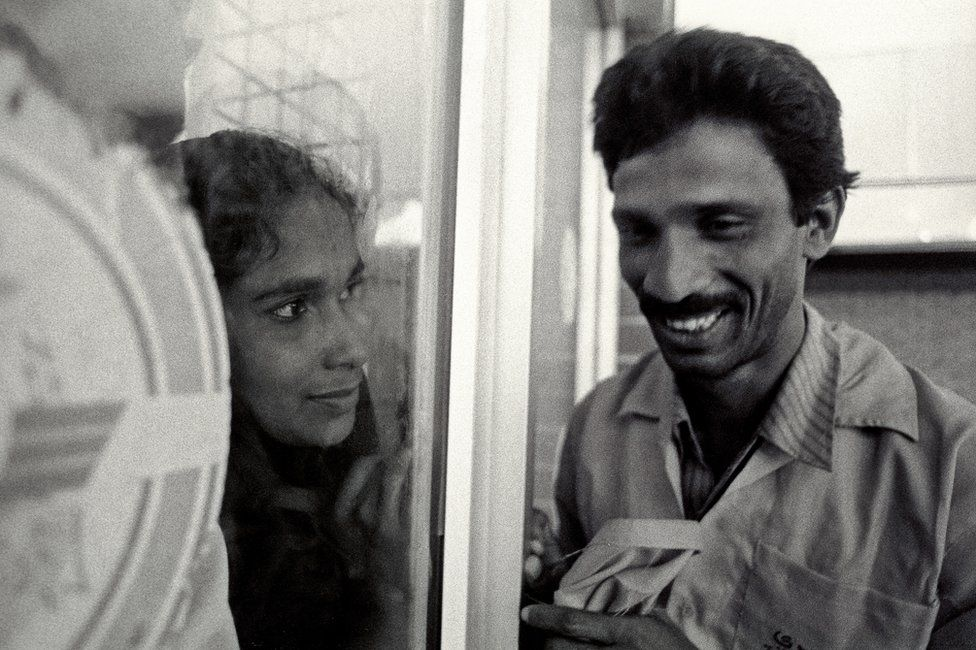 A woman looks at her husband through a window at Dhaka airport