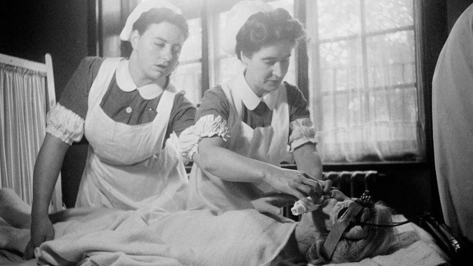 Nurses attending to a patient receiving electro-convulsive therapy to cure depression in 1946
