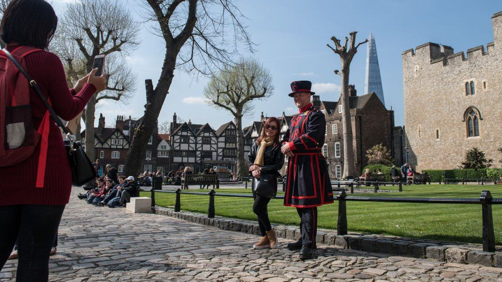 Tourists have photos taken with a Beefeater at the Tower of London