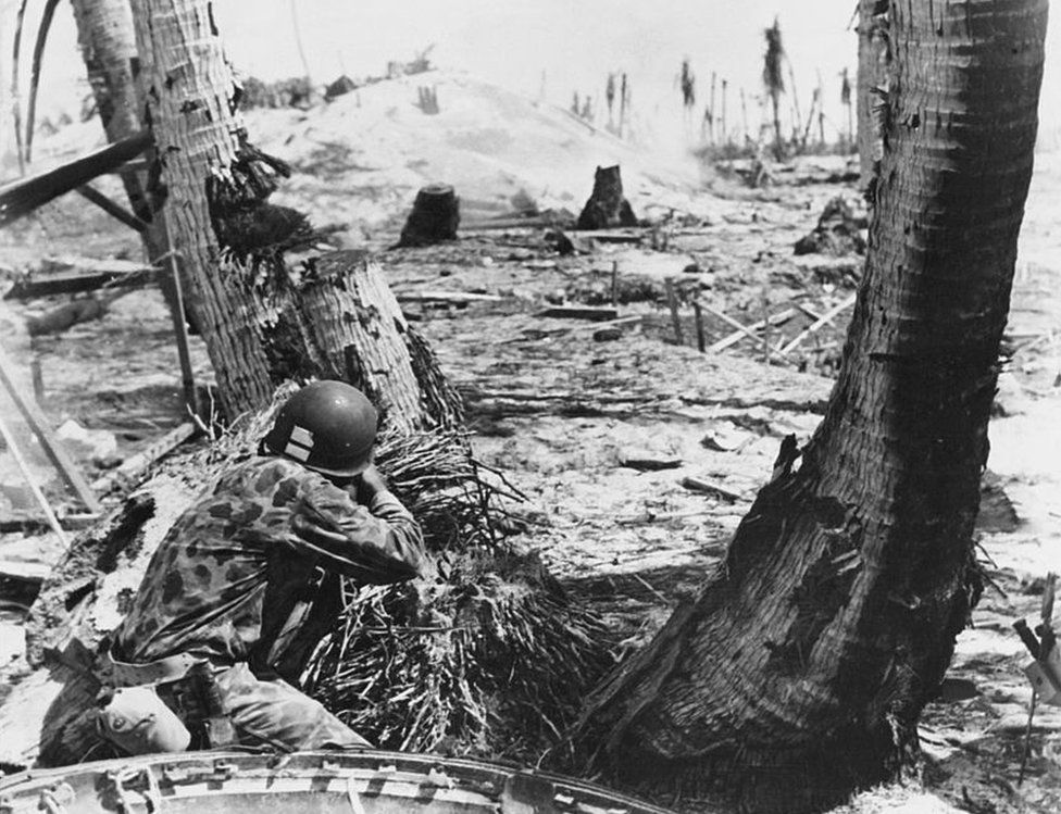 A US Marine fires at a Japanese pillbox bunker