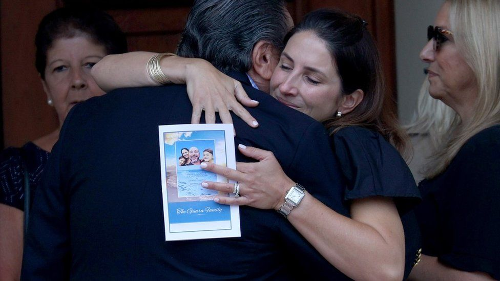 Mourners hug at the funeral