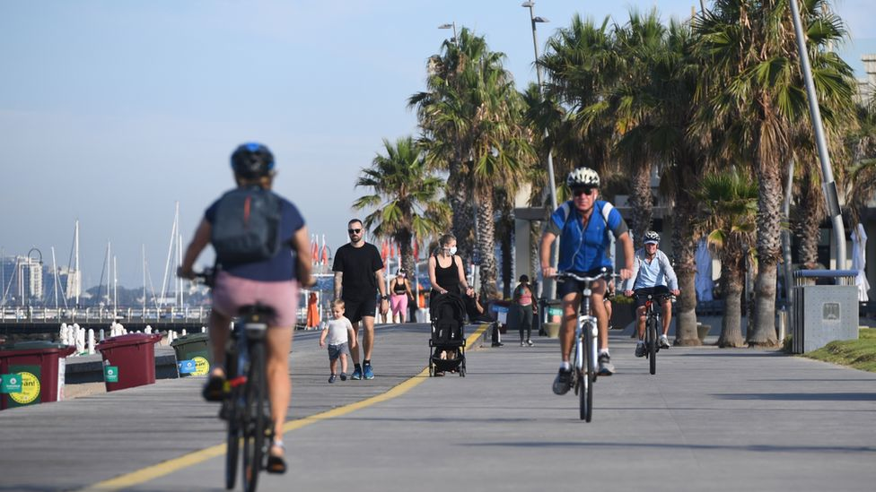 People cycling along a promenade in Melbourne during the February lockdown