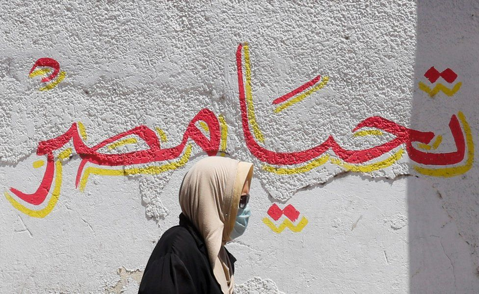 """A woman wearing a protective face mask walks past a wall that has the words """"Long live Egypt"""" painted in red and yellow."""