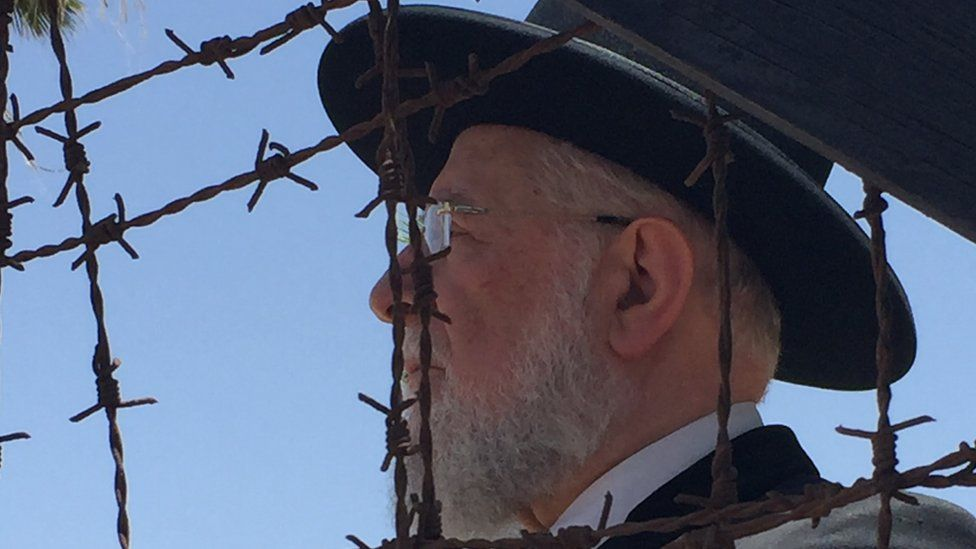 Rabbi Meir Lau looks through the barbed wire at the former British internment camp at Atlit