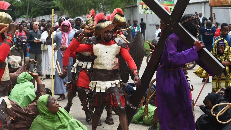 A man enacting Jesus Christ receives a beating as he carries a cross during a procession to mark Good Friday in Lagos, on April 14, 2017.