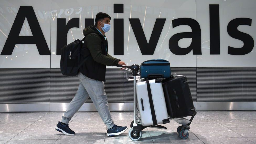 Passenger arriving in Heathrow Airport wearing a face mask