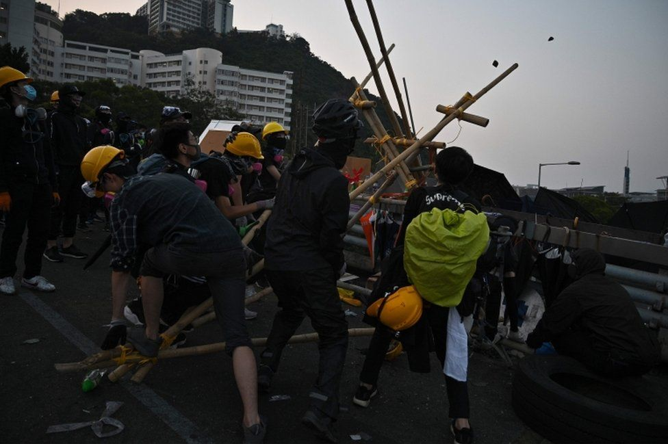 Black-clad protesters try using a catapult made with bamboo at the Chinese University of Hong Kong on November 13, 2019.