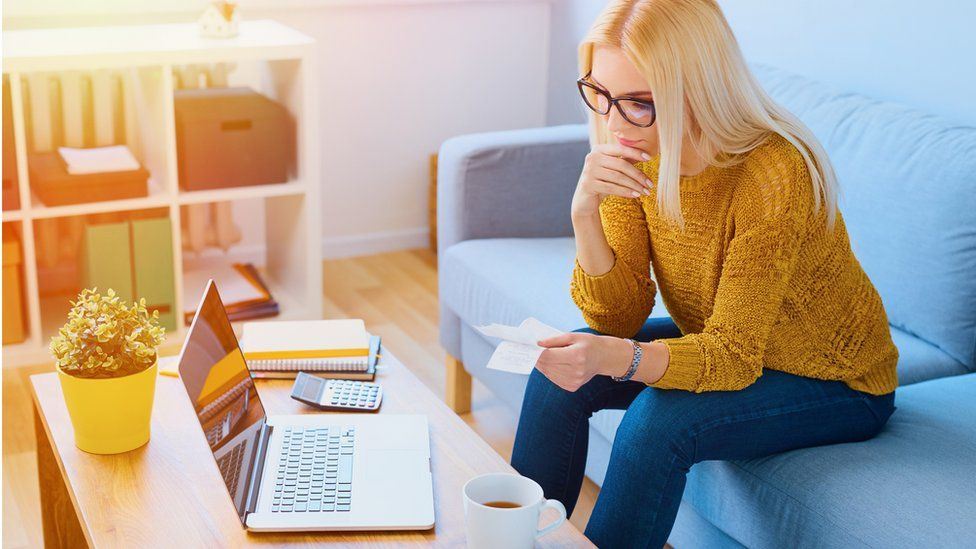 Woman sitting at home counting expenses