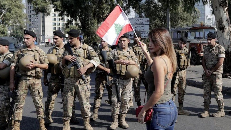 A woman waves a Lebanese flag in front of soldiers in Tripoli, Lebanon. Photo: 22 October 2019