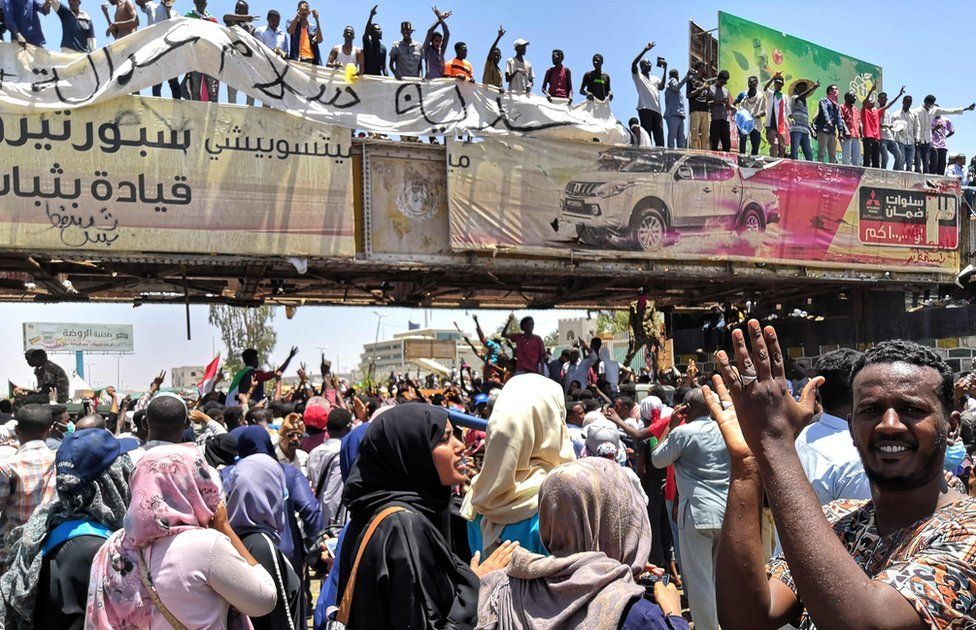 """Sudanese protesters rally in front of the military headquarters in the capital Khartoum on April 8, 2019. - Sudan""""s army deployed around its Khartoum headquarters Monday as thousands of protesters urging the military to join calls for leader Omar al-Bashir""""s resignation defied tear gas to demonstrate for a third day, witnesses said."""