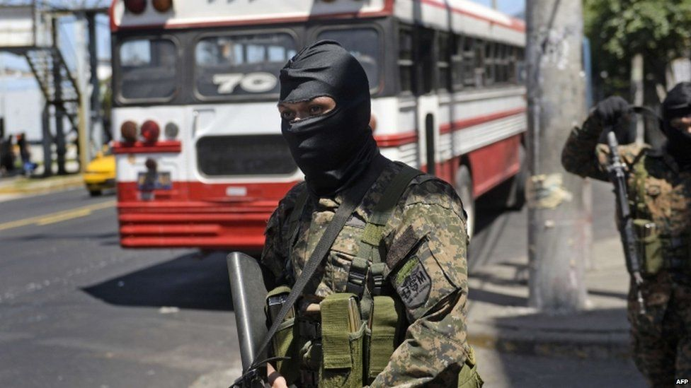 Soldiers of the Reaction Special Forces stand guard near one of the few buses that circulates in San Salvador on July 30, 2015