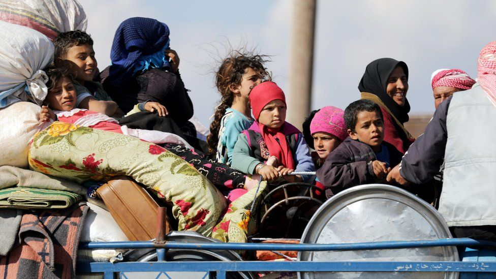 Displaced Syrians sit on a lorry in the town of Inab, in the Afrin region (12 March 2018)