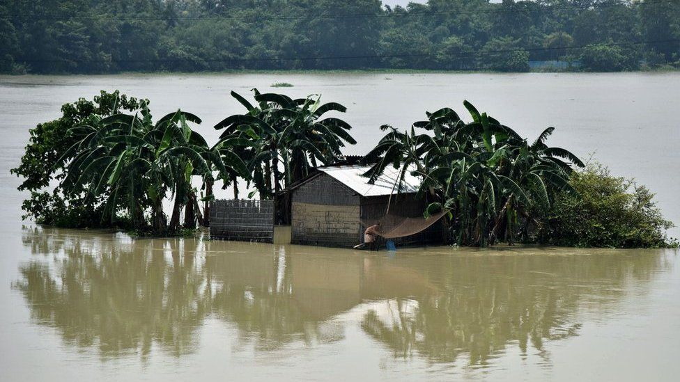 An Indian villager surrounded by floodwaters in Assam in August 2017