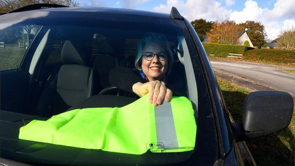 Jacline Mouraud poses in her car putting a yellow vest on the dashboard in Bohal, western France, on 13 November 2018