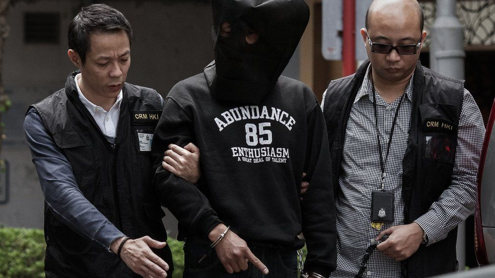 Hong Kong attack; One of the two assailants helps police inspect the scene of crime