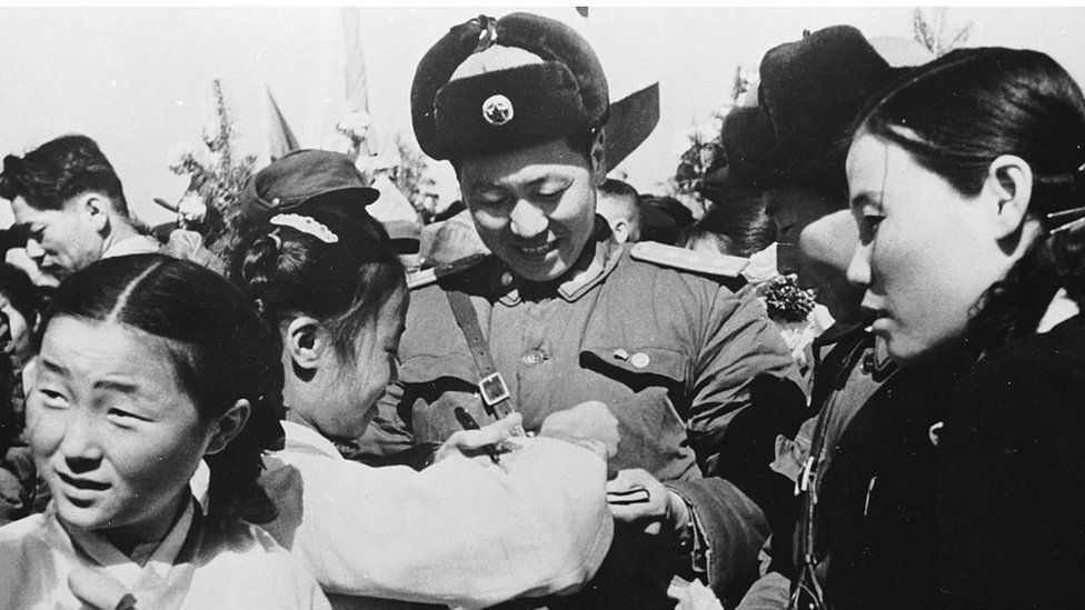 29 March 1958: Korean girls present a member of the Chinese People's Volunteer Army with a bouquet of flowers prior to the mass withdrawal of Chinese troops from North Korea