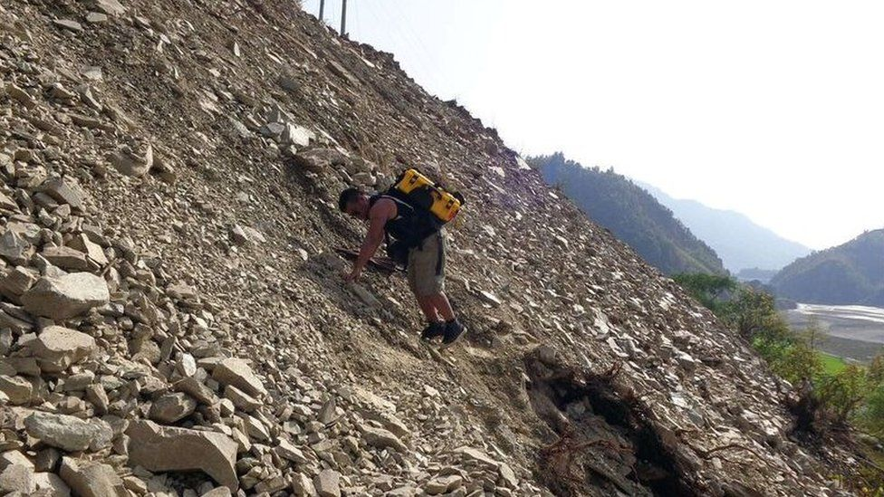 Man climbing rubble in earthquake aftermath with yellow solar suitcase strapped to his back