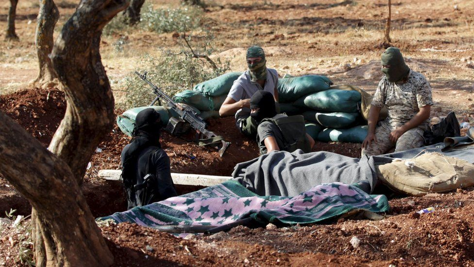 Members of al-Qaeda's Nusra Front sit in a trench in north-west Syria