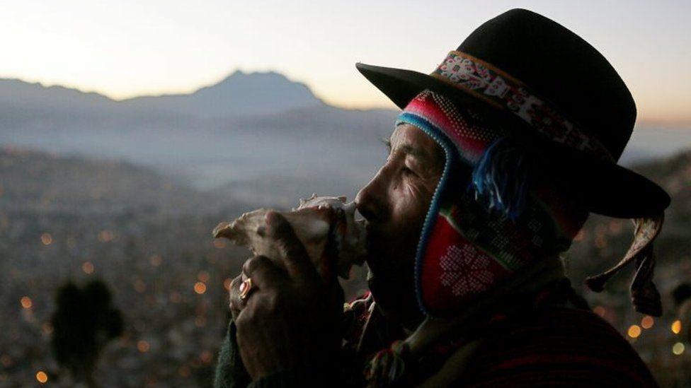 An Aymara man blows into a shell during a ceremony in El Alto near La Paz, Bolivia, June 21, 2016