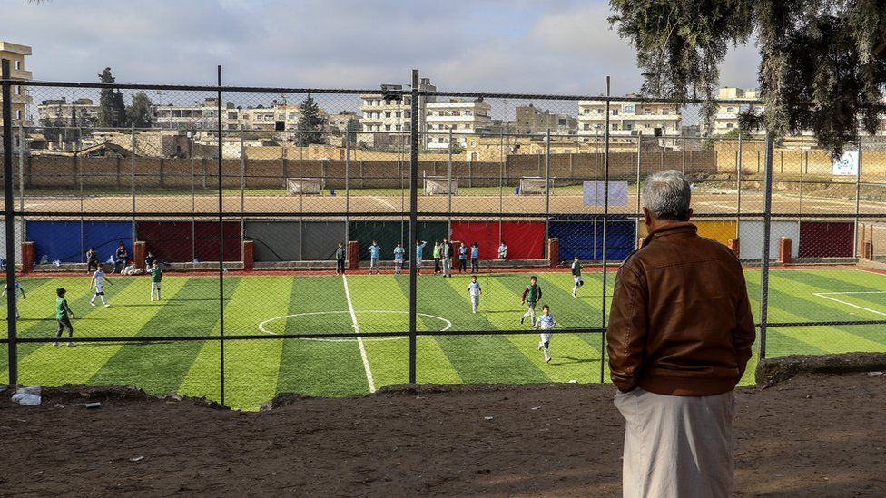 A man watches a football match in Manbij, northern Syria (31 December 2018)