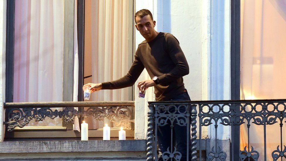 Mohamed Abdeslam lighting candles at the window of the family home during a vigil for the dead in Brussels