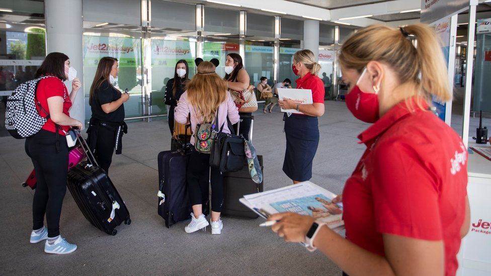 British tourists walk with their luggage outside the airport upon their arrival to Palma de Mallorca on Monday
