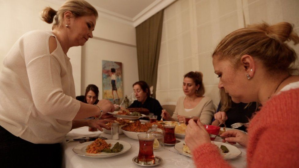 Emel Resuloglu serves her friends during their monthly get-together