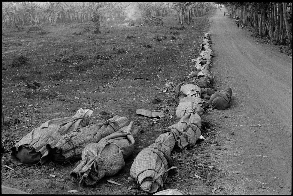 Wrapped up bodies line a dirt path