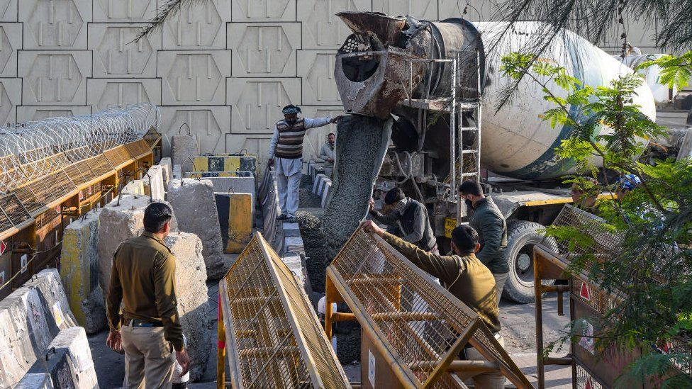 Concrete being poured between stone barricades