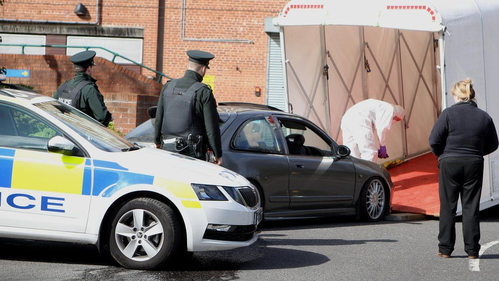 Police officers look on as a grey MG car is driven into a forensic van to be taken away from Belfast City Hospital