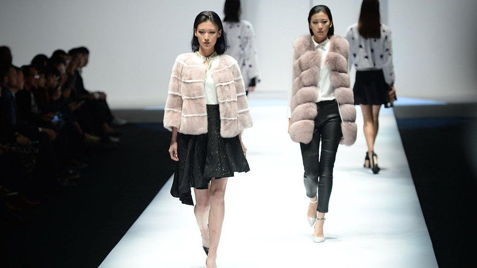 A model showcases designs on the runway during a fashion show in Beijing