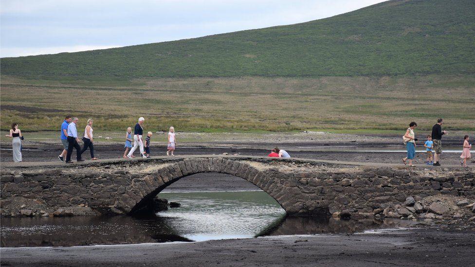People walking across the bridge at Spelga Reservoir