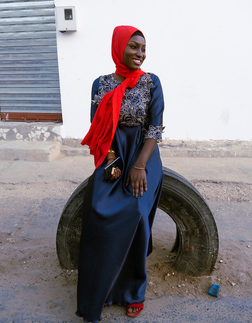 Dienaba Balde wears a blue outfit plus red accessories