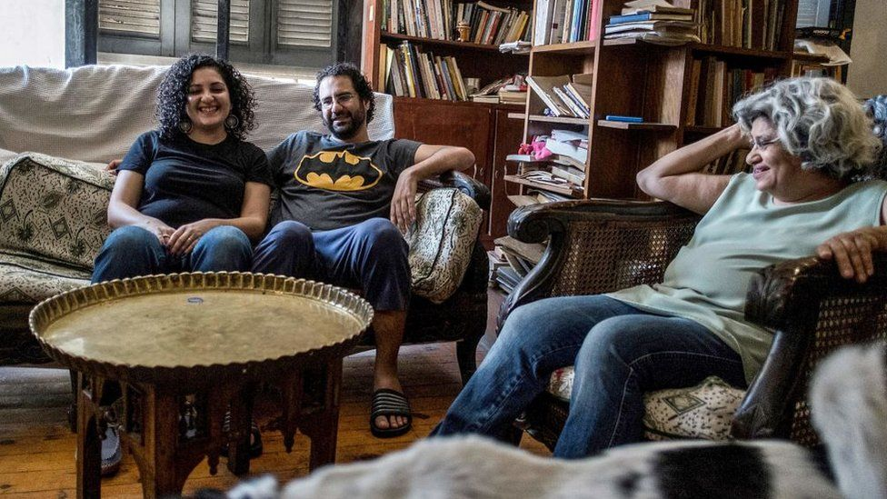 Egyptian activist and blogger Alaa Abdel Fattah (C) smiles next to his mother Laila Soueif (R) and sister Mona Seif (L) in Giza (17 May 2019)