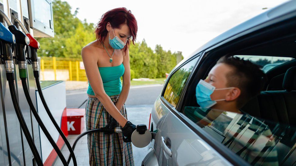 Woman filling up car with petrol with a child sitting in the car.