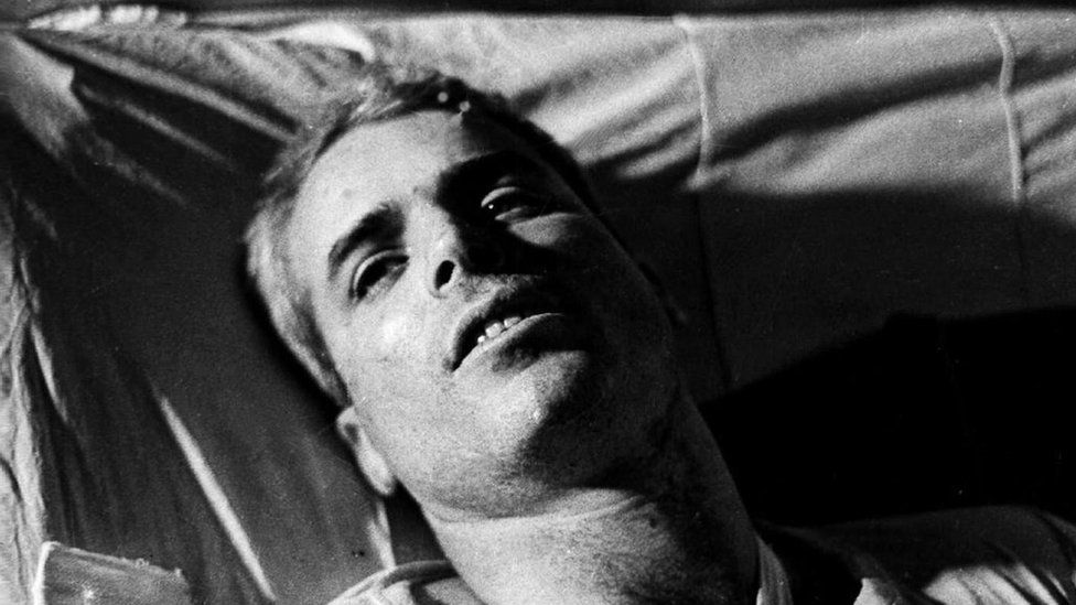 This file picture taken in 1967 shows US Navy Airforce Major John McCain lying on a bed in a Hanoi hospital as he was being given medical care for his injuries.
