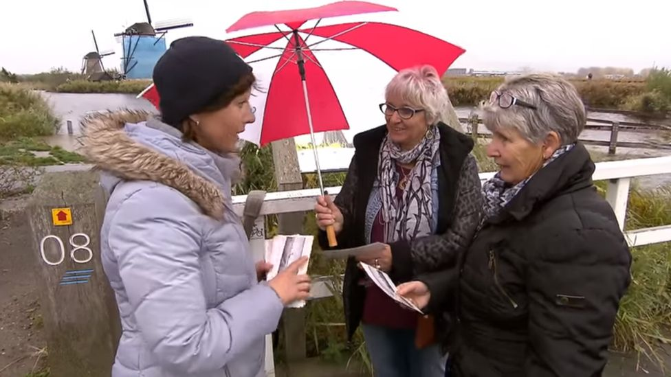 Kinderdijk inhabitant hands cards to tourists, Netherlands