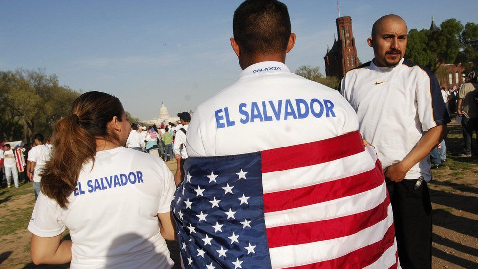 A protester wearing T-shirt that reads El Salvador and with a US flag draped over his shoulders during an immigration rally on the National Mall 10 April 2006 in Washington