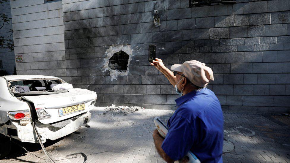 Seorang pria Israel mengambil foto dengan ponselnya dari sebuah bangunan tempat tinggal yang terkena roket yang diluncurkan dari Gaza, di Ashkelon, Israel 14 Mei 2021