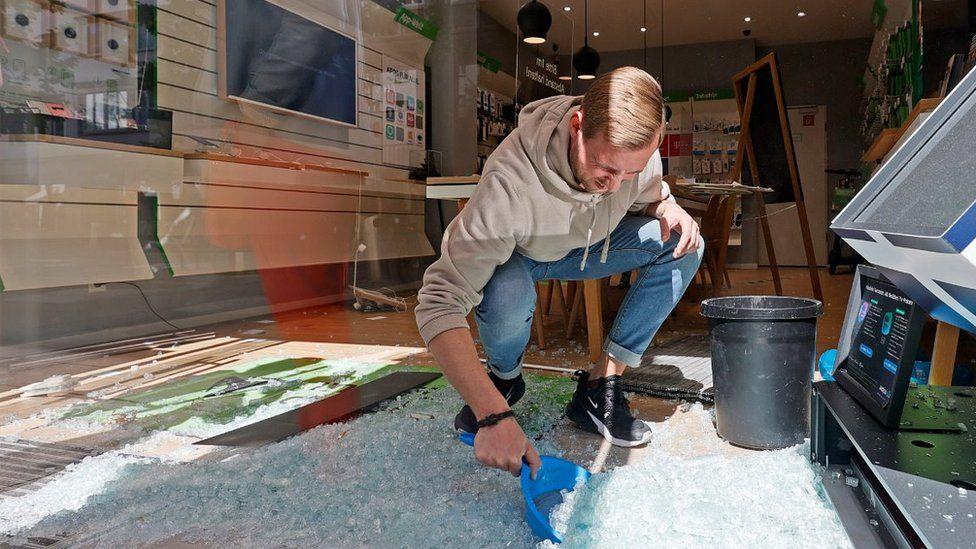 Sweeping up broken glass in a shop, 21 Jun 20