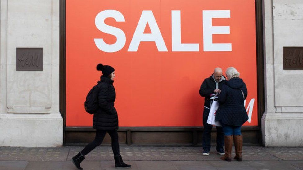 Shoppers walking past sale sign
