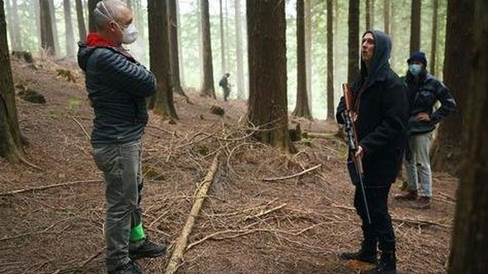 A crew member wears a mask, while an actor holds a fake rifle, surrounded by forest